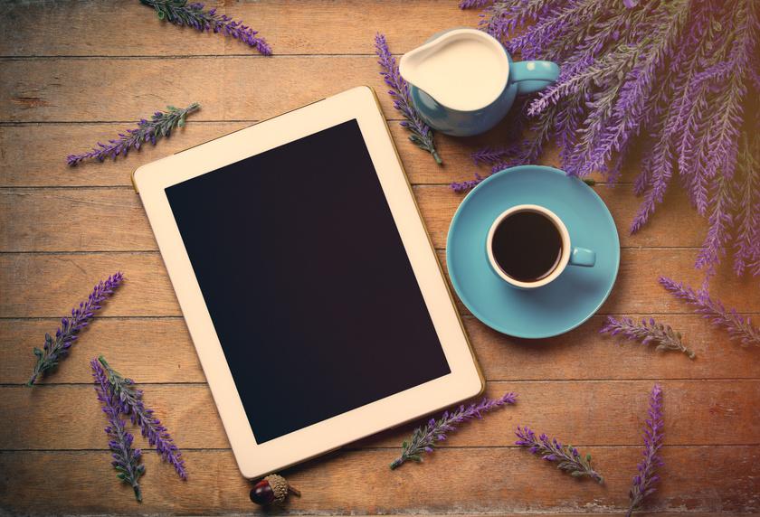 Tablet mit Kaffee und Milch auf Holztisch